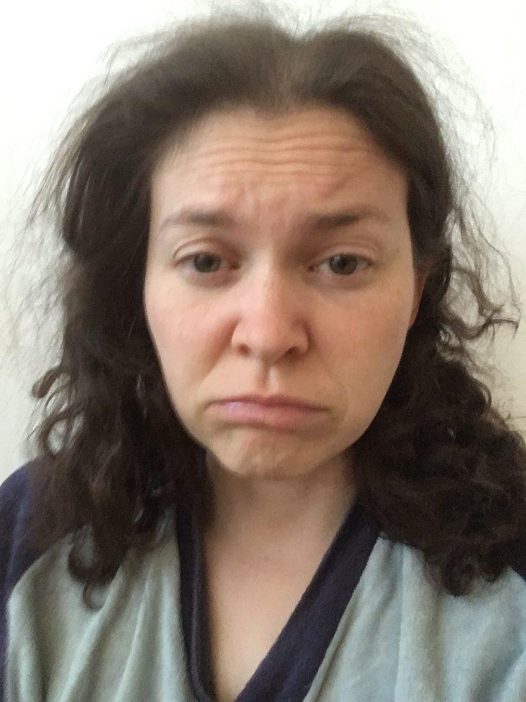 Judith mit zerzausten Haaren im Schlafanzug. Gesichtsausdruck zerknirscht