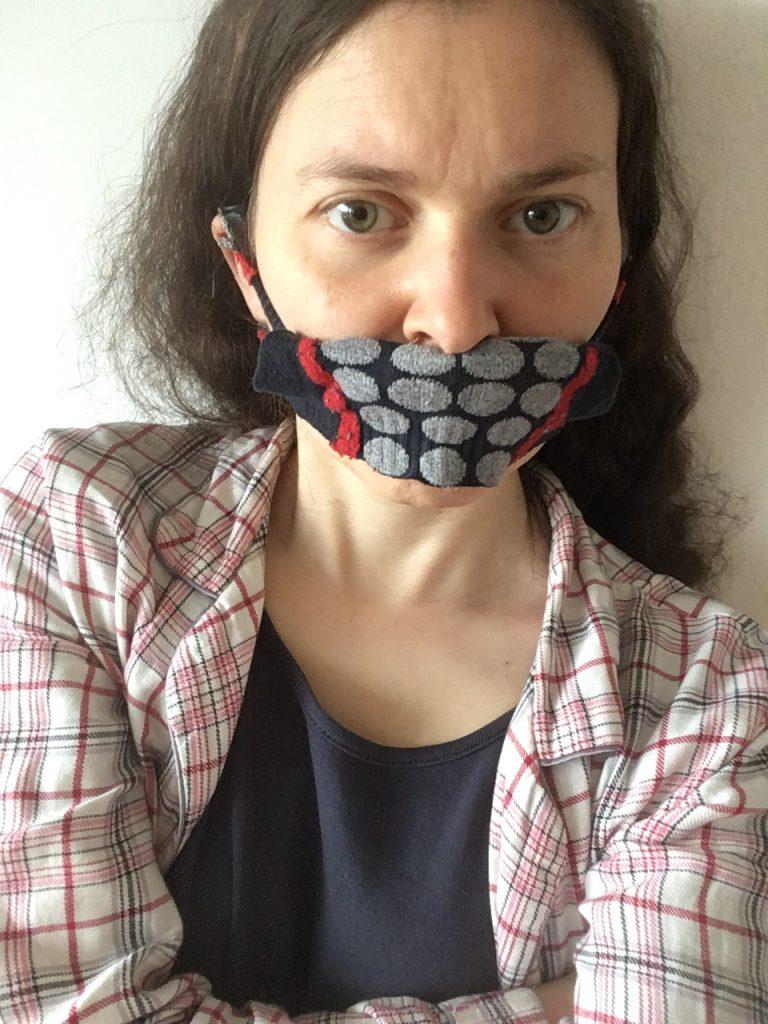 Judith mit kritischem Blick. Ein schwarzer Mund-Nasen-Schutz mit grauen Punkten ist nur über den Mund gezogen. Die Arme sind verschränkt.