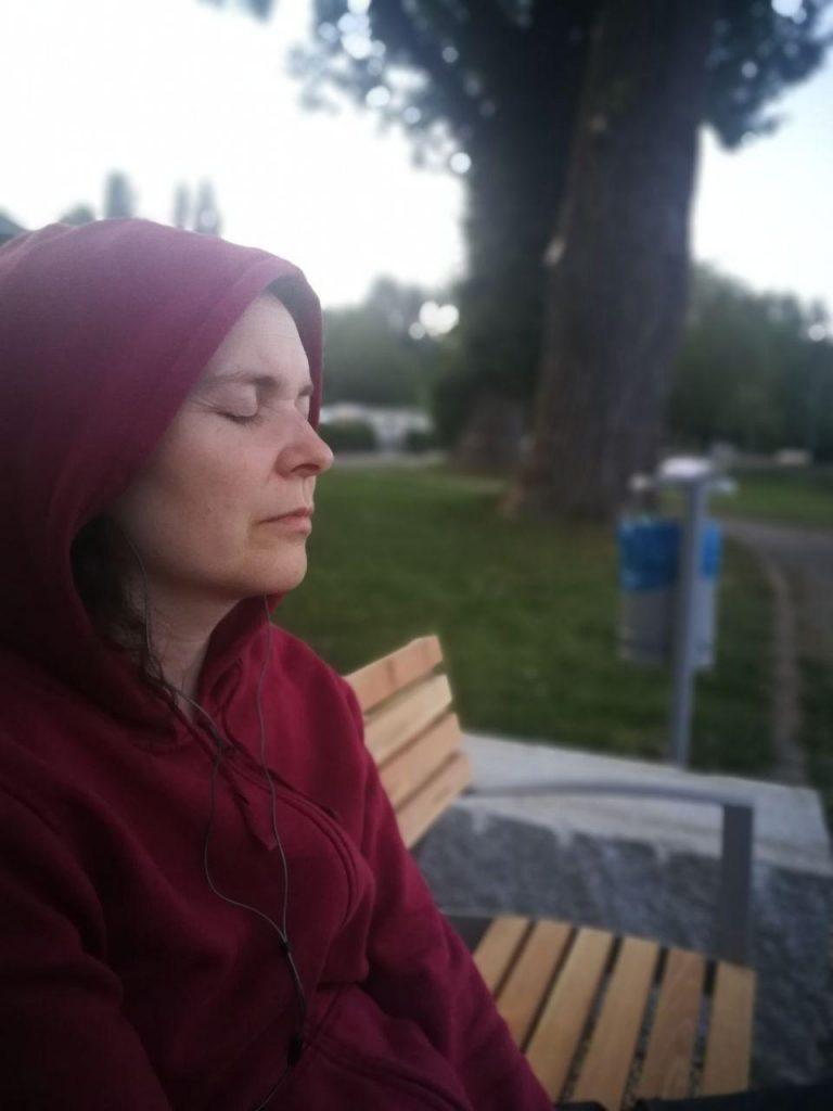 Judith mit Kapuze auf einer Bank, die Augen geschlossen