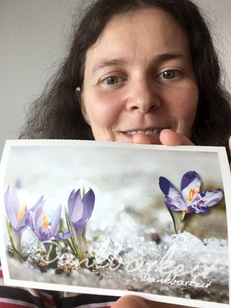 """Judith hält eine Postkarte mit Blumen hoch - darauf der Text """"Dankbarkeit"""" - Symbol für """"das was du hast, mehr wertschätzen"""""""