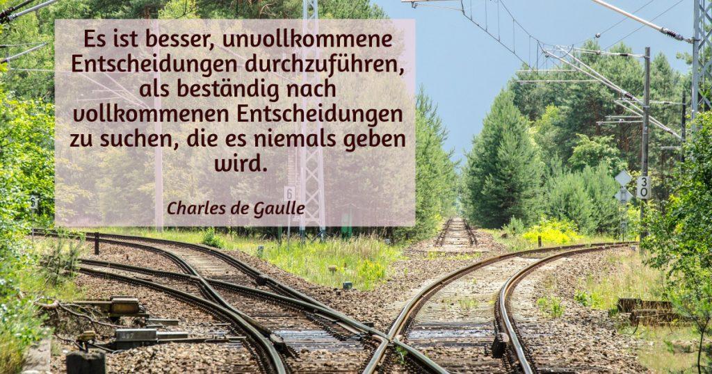 Eisenbahngleise in drei Richtungen.  Zitat: Es ist besser, unvollkommene Entscheidungen durchzuführen, als beständig nach vollkommenen Entscheidungen zu suchen, die es niemals geben wird. Charles de Gaulle