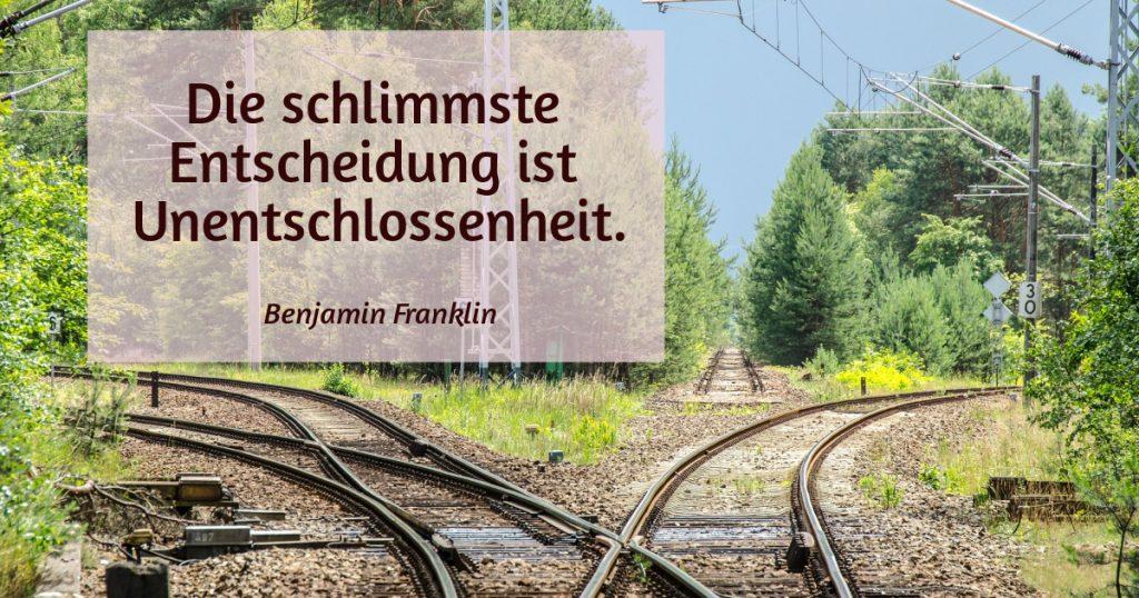 Eisenbahngleise in drei Richtungen. Zitat: Die schlimmste Entscheidung ist Unentschlossenheit. Benjamin Franklin