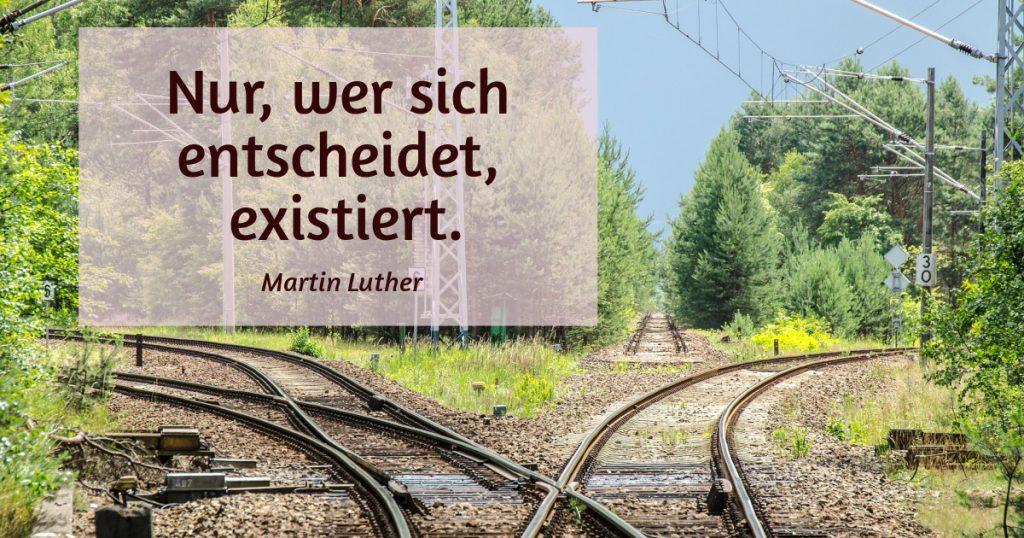 Eisenbahngleise in drei Richtungen. Zitat: Nur, wer sich entscheidet, existiert. Martin Luther