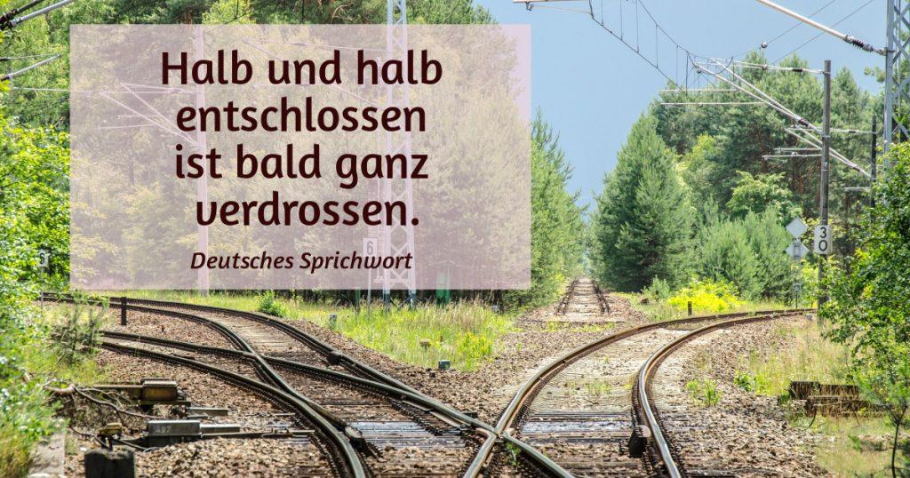 Eisenbahngleise in drei Richtungen. Zitat: Halb und halb entschlossen ist bald ganz verdrossen. (deutsches Sprichwort)
