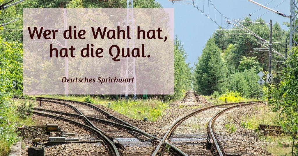 Eisenbahngleise in drei Richtungen. Zitat: Wer die Wahl hat, hat die Qual. (deutsches Sprichwort)