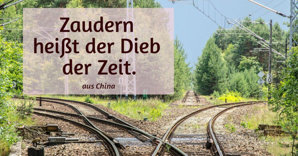 Eisenbahngleise in drei Richtungen. Zitat: Zaudern heißt der Dieb der Zeit. (aus China)