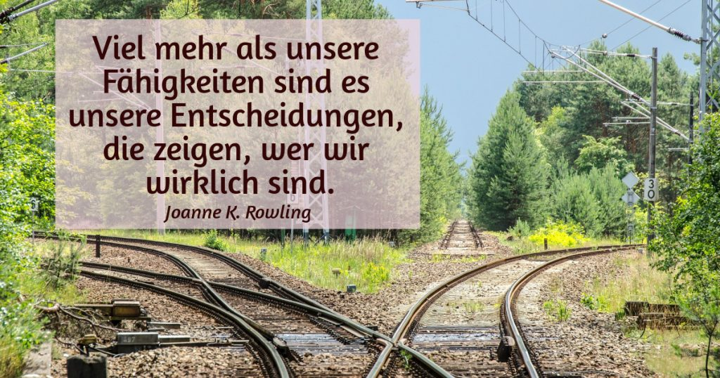 Eisenbahngleise in drei Richtungen. Zitat: Viel mehr als unsere Fähigkeiten sind es unsere Entscheidungen, die zeigen, wer wir wirklich sind. Joanne K. Rowling